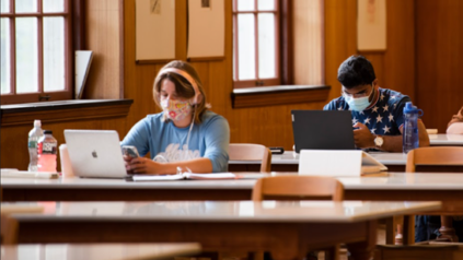 Two students wearing masks study at different tables in the main reading room of Fogler Library.