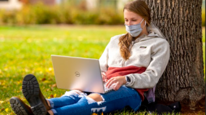 A masked female student wearing blue jeans and a white and red jumper leans against a tree, working on her laptop computer.