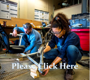A student kneels down working on a mechanical task, next to another student. They are in a workshop.