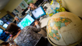 A globe is in focus at the front of a classroom, with people working on maps and computers in the background.
