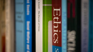 """Books lined up on a shelf, with one titled """"Ethics"""" in focus."""