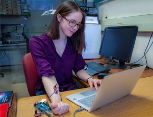 Nicole McGrath tests the EMG (electromyography) unit she designed for her research work.