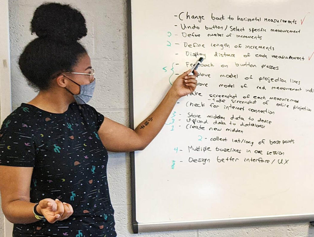 A woman points at a dry erase board