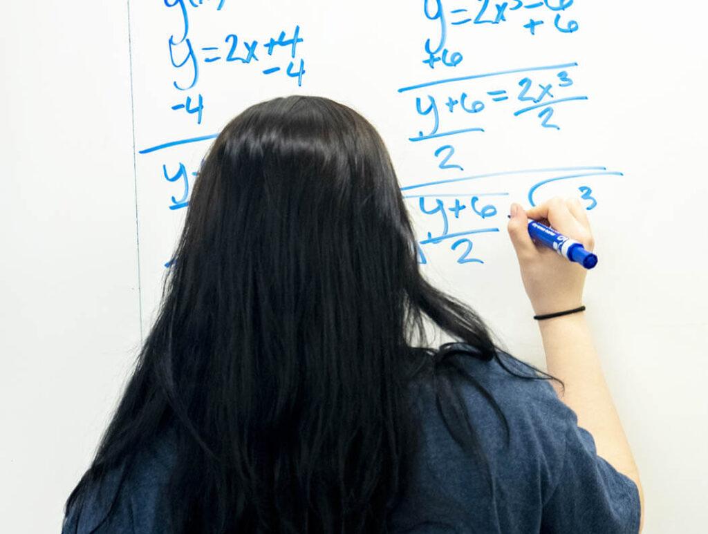 A woman writes on a dry erase board