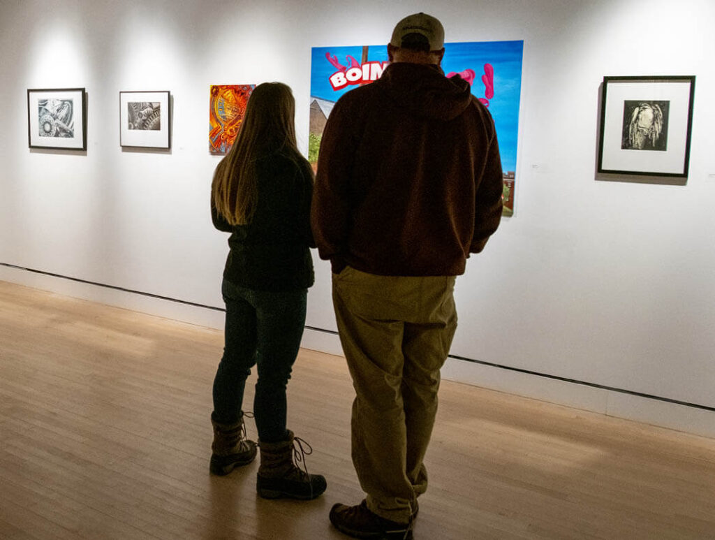 Two people look at artwork on in a gallery