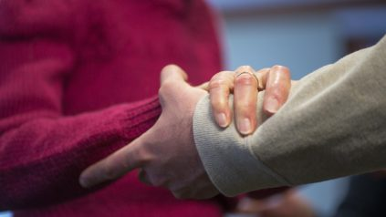 Elderly woman hold hand with man
