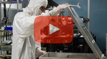 Play button over researcher in cleanroom