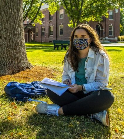 A woman wearing a mask is sitting outside on UMaine's Mall
