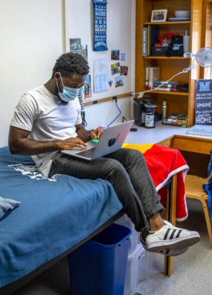 Male student studying on a laptop in a dorm room
