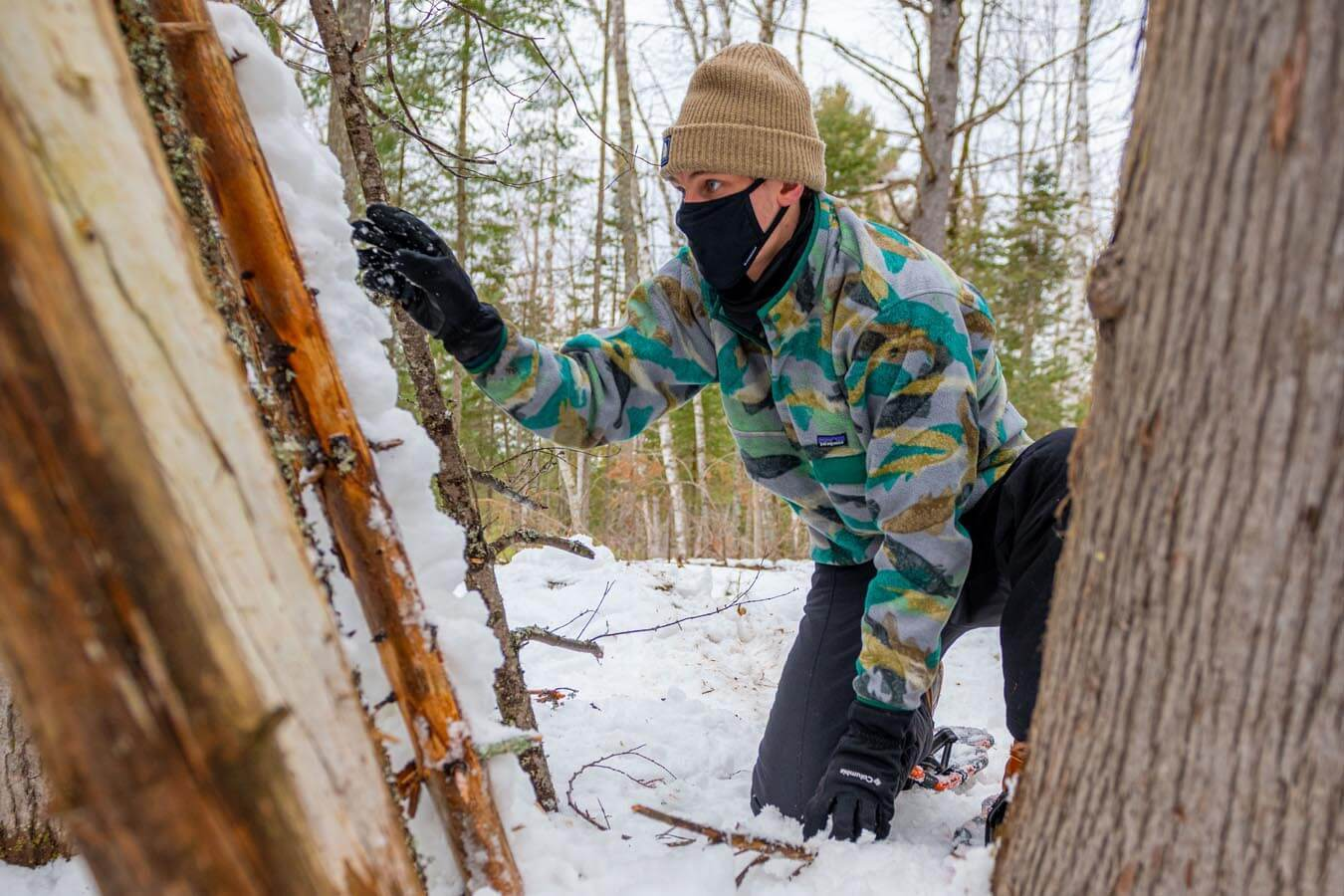 An outdoor leadership student builds a snow shelter in Demeritt Forest.