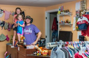 father and two daughters posing behind the counter at a thrift store