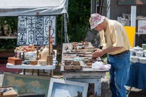 older man inspecting used tools at a flea market