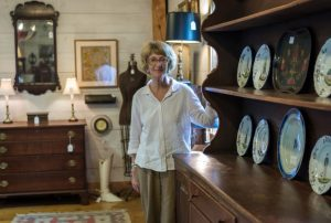 older woman posing by a dining hutch at an antique store