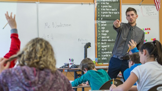 Student teacher pointing to a student's raised hand