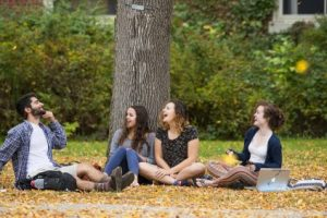 students sitting under a tree laughing
