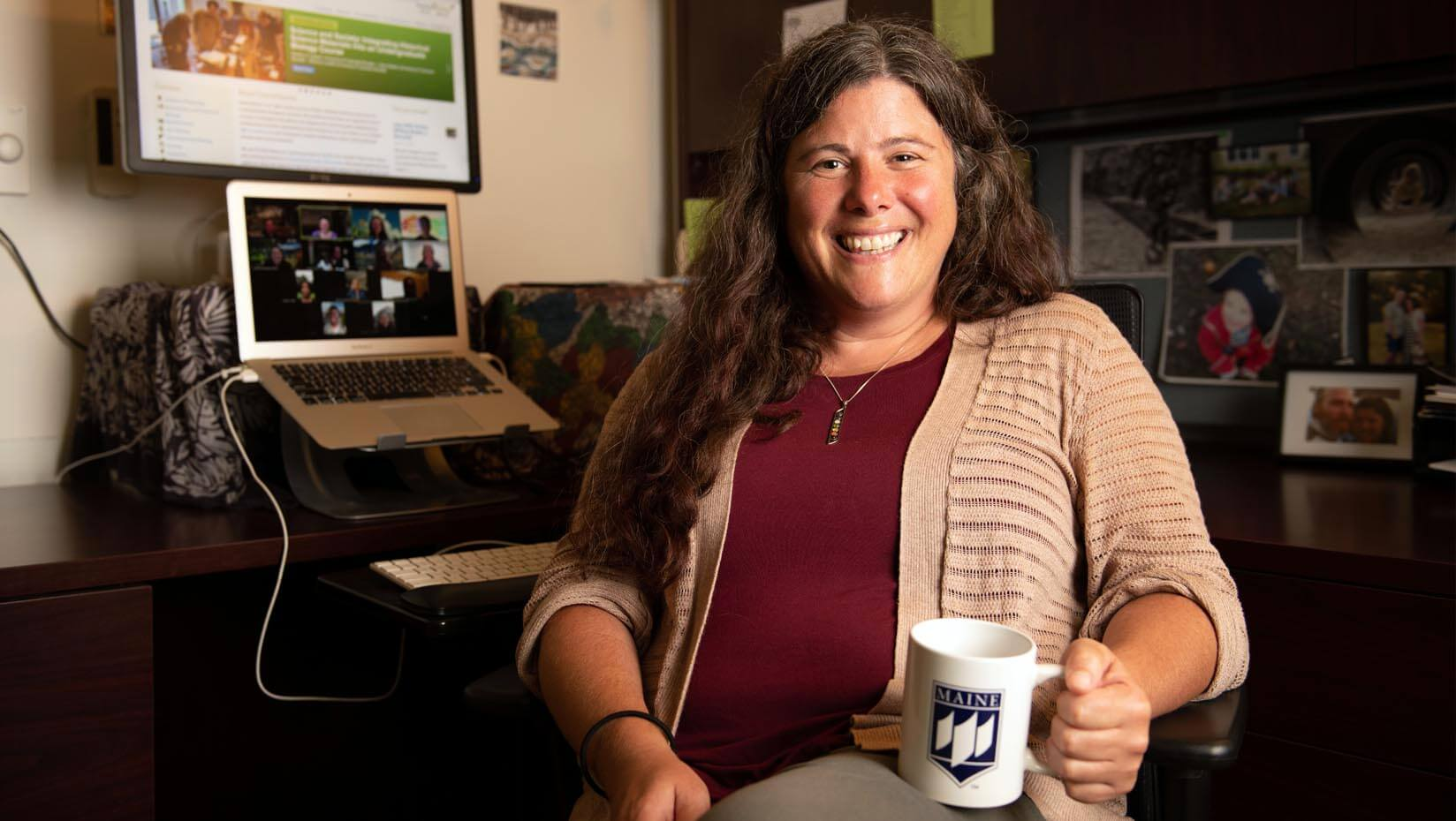 Erin Vinson sits in her office holding a UMaine coffee mug