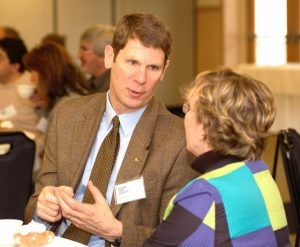 Dr. Jeff Hecker chatting with Dr. Linda Silka at a Rising Tide event.