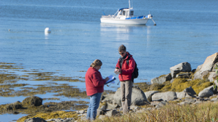 Two scientists conducting marine science research on the coast of Maine
