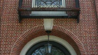 Metal balcony above arched door