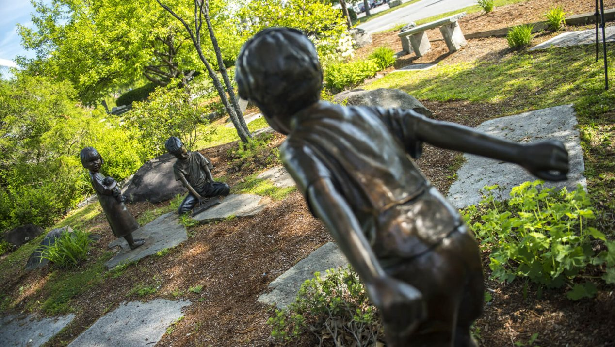 Statues of children playing in UMaine's rose garden