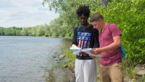 two smart students collaborate, looking at sampling instructions near the river