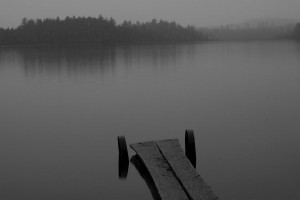 Due to a warm winter in Maine, an ice cutting dock floats upon Whipple, Pond.