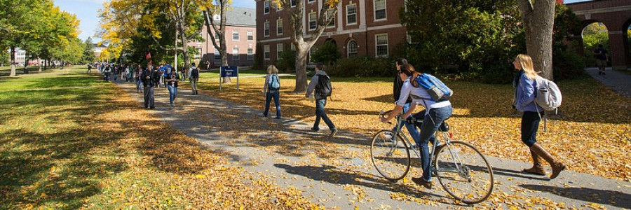 Students riding bikes and walking through the university mall in the fall