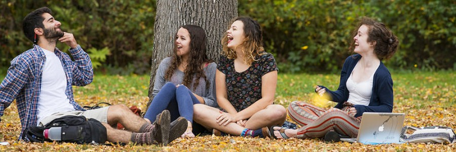 Students sitting on the ground laughing