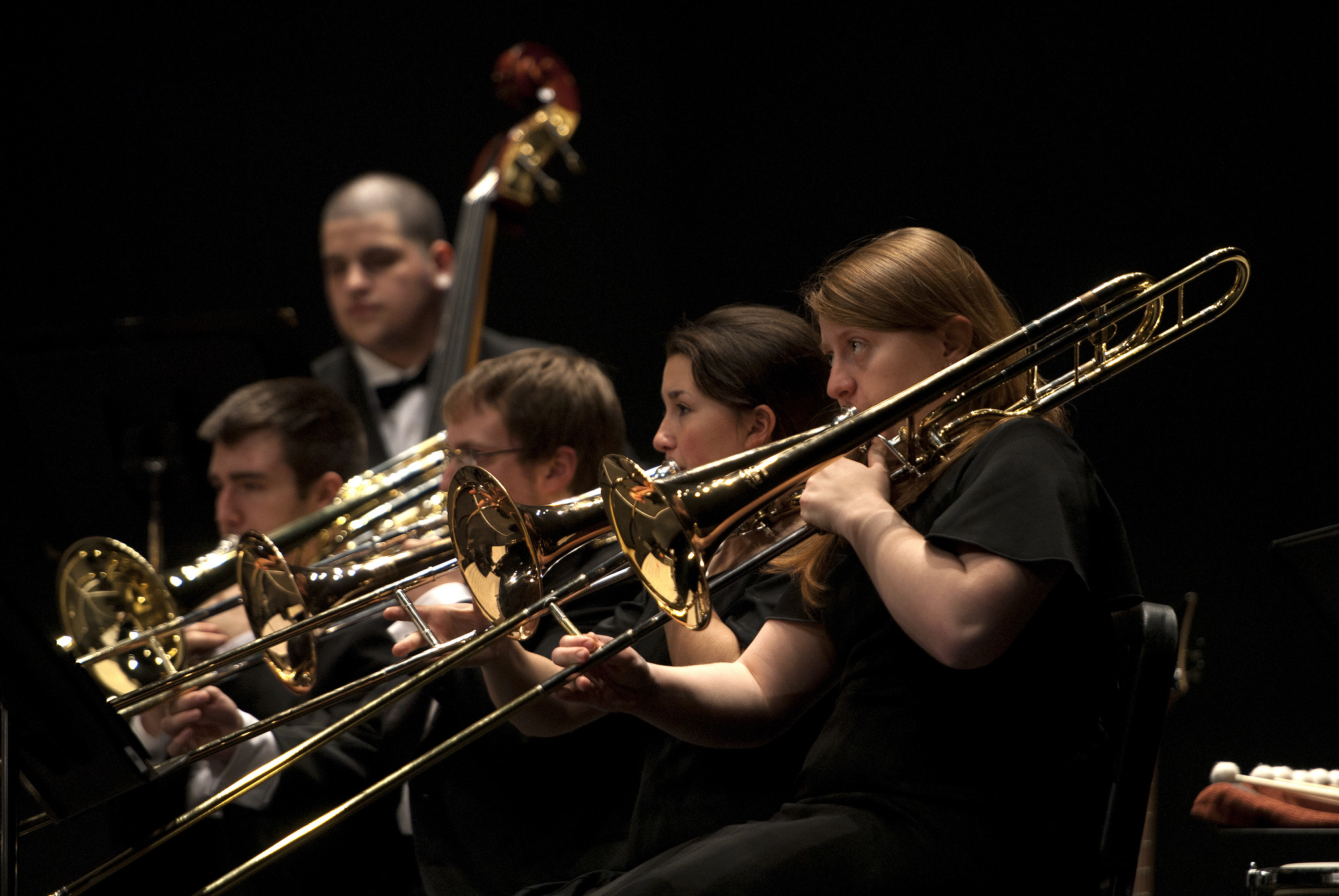 four people playing the trombone at a concert
