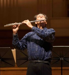 Robert Dick playing the flute on a concert stage