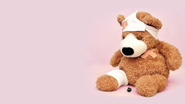wounded teddy bear in front of pink background