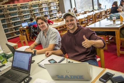 two smiling male students working on laptops in library