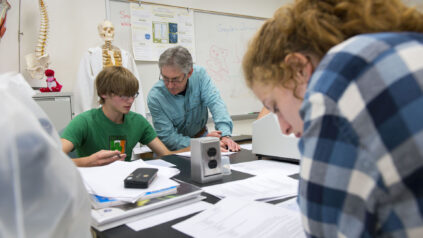 male teacher helps male teen in a science lap in front of a female teen who looks at her textbook
