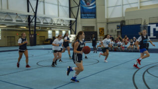 A group of young teen girls playing basketball at a basketball summer camp in Orono Maine