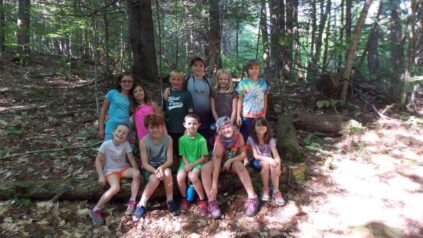 Kids standing in a the woods at a summer camp in Maine