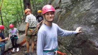 A teen boy smiling while holding a boulder at Bryant Pond Maine Summer Camp in