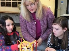 A female instructor helps two female students at an engineering summer camp in Orono Maine