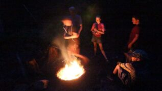 Teens standing around a campfire at Greenland Point summer camp in Princeton Maine