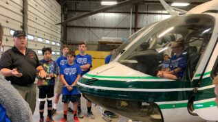 A group of young kids looking at a helicopter during the Maine Summer Transportation Institute summer camp in orono Maine