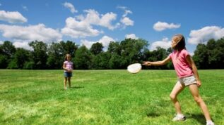 Young girls playing frisbee in an open field at RAD summer camp in Orono Maine