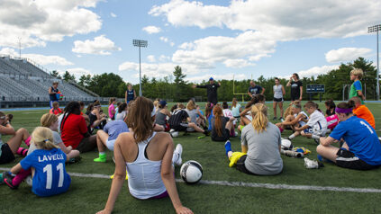 students sitting on field at soccer camp