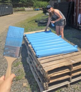 Americorps volunteers painting dumpster lids light blue to make them stand out.