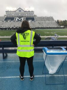 A zero-waste team member posing in front of the Alfond Stadium field