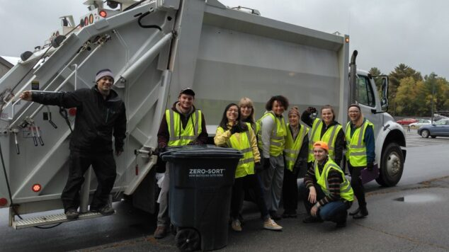 The zero-waste team in front of the recycling compactor truck