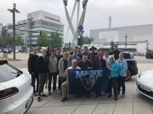 Students outside factory in Germany with UMaine banner