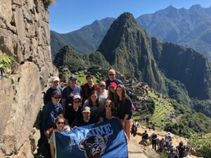 Student on mountainside in Peru with UMaine banner
