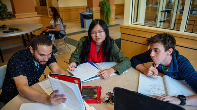 group of three students studying at table