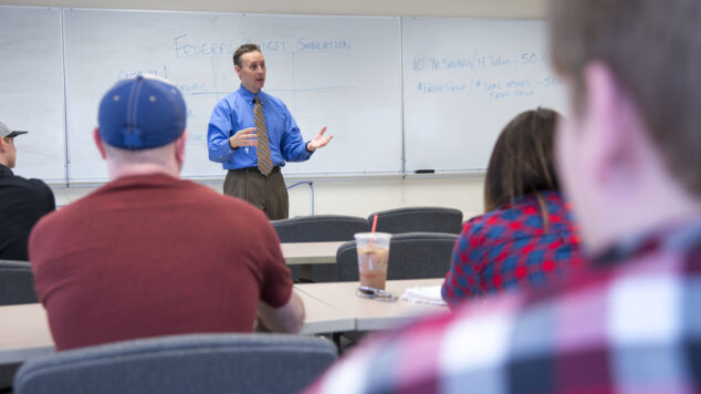 Professor in front of white board addressing a classroom of students