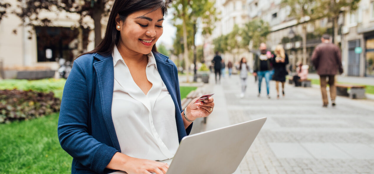 Beautiful Asian woman sitting at the street and shopping online.