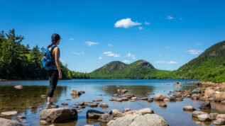 A female hiker exploring Jordan Pond in Acadia National Park, Maine.